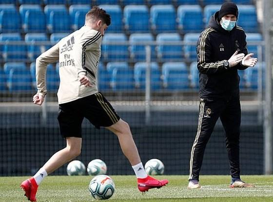 HLV Zinedine Zidane đeo khẩu trang khích lệ cầu thủ tập luyện giữa mùa dịch bệnh. Ảnh: Getty Images