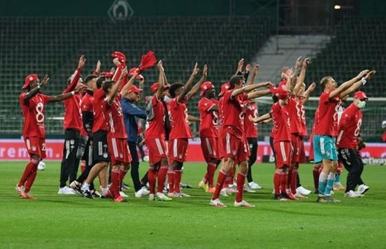 Bayern hướng về khán đài trống chia sẻ vinh quang với người hâm mộ. Ảnh: Getty Images