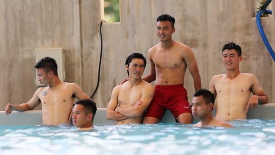 Các cầu thủ thư giãn trong bể bơi trước khi xả trại đi mua sắm. Ảnh: Tùng Lê