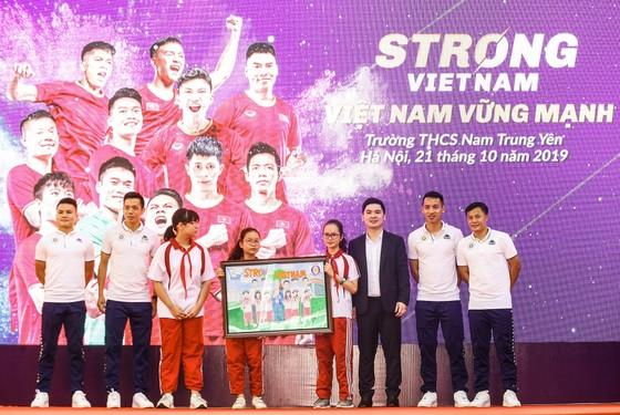 """Các cầu thủ CLB bóng đá Hà Nội và Trưởng Ban tổ chức chương trình """"Strong Vietnam"""" Đỗ Vinh Quang nhận quà là bức tranh từ các em học sinh THCS Nam Trung Yên"""