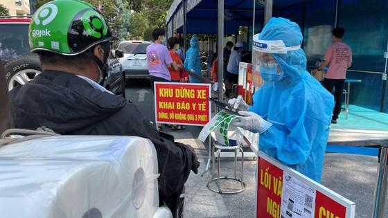 Nhân viên y tế hỗ trợ người dân khai báo y tế khi đến khám chữa bệnh tại Bệnh viện 175. Ảnh: HOÀNG HÙNG
