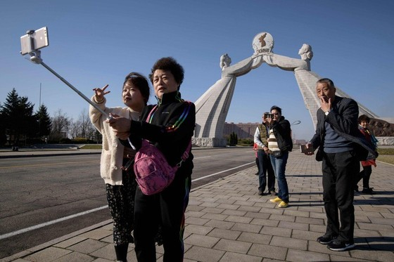 Tourists from China pose for photos before the Three Charters monument in Pyongyang in April 2019. Photo: AFP