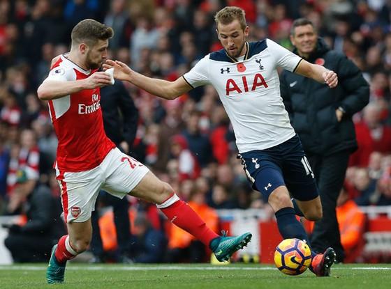 Shkodran Mustafi (trái, Arsenal) ngăn chặn pha tấn công của Harry Kane (Tottenham)