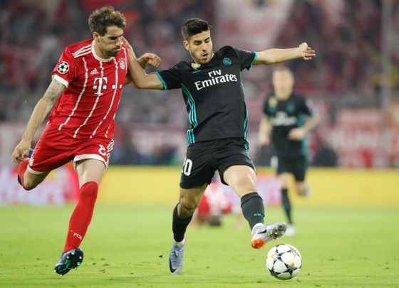 Marco Asensio (phải) vượt qua J. Martinez của Bayern Munich.