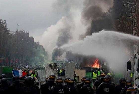 Người biểu tình đối đầu với cảnh sát tại Đại lộ Champs-Élysées. Ảnh: REUTERS