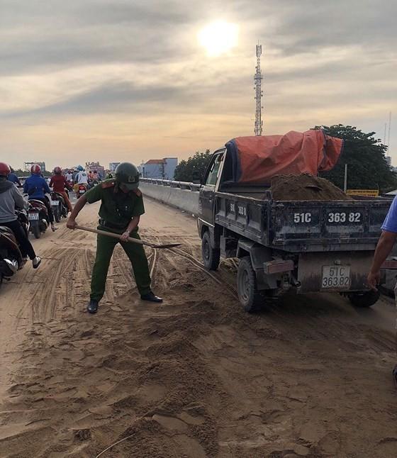 Cảnh sát giao thông - trật tự TPHCM dọn cát rơi trên đường ảnh 1