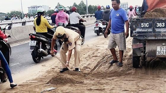 Cảnh sát giao thông - trật tự TPHCM dọn cát rơi trên đường ảnh 3