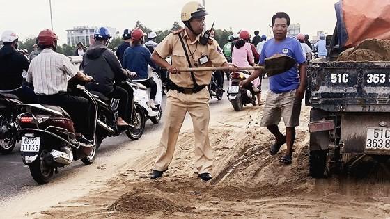 Cảnh sát giao thông - trật tự TPHCM dọn cát rơi trên đường ảnh 4