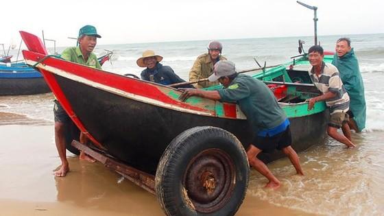 Ngư dân ở xã Cẩm Dương (Hà Tĩnh) đưa thuyền vào bờ tránh bão. Ảnh: DƯƠNG QUANG