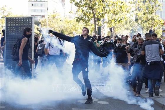 Người biểu tình bạo lực ném hơi cay trong cuộc tuần hành chống biến đổi khí hậu tại Paris, Pháp, ngày 21-9-2019. Ảnh: TTXVN