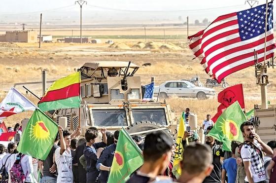 Người Kurd tại Syria vây quanh xe quân sự của Mỹ ở ngoại ô thị trấn Ras al-Ain, tỉnh Hasakeh (Syria), gần biên giới Thổ Nhĩ Kỳ