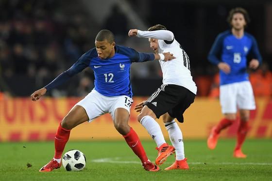 Kylian Mbappe (trái, tuyển Pháp) kiểm soát bóng trước Mesut Oezil (Đức).. Ảnh: Getty Images.