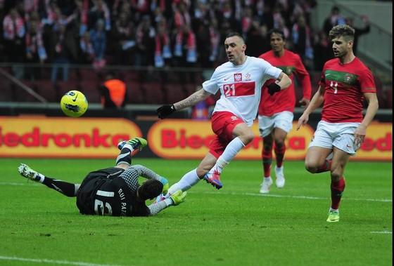 Tiền vệ Ireneusz Jeleri (Ba Lna) sút bóng trước thủ thành Rui Patricio (Bồ Đào Nha)