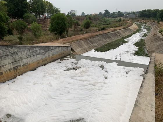 Bọt nổi trắng xóa trên kênh sau mưa lớn ảnh 1