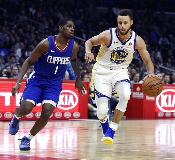 Stephen Curry (phải) trước sự theo đuổi của một cầu thủ LA Clippers
