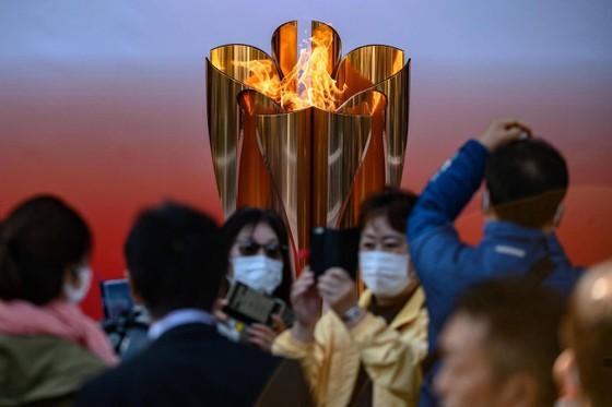 Nhiều du khách đeo khẩu trang vẫn đến thăm đài lửa Olympic Tokyo