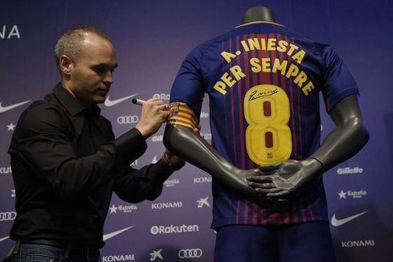 """Andrea Iniesta ký vào chiếc áo lưu niệm bản hợp đổng :""""suốt đời"""" với Barcelona. Ảnh: Getty Images."""