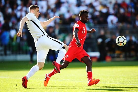 Tiền đạo Chris Wood (trái, New Zealand) gây áp lực cho hàng thủ Peru. Ảnh: Getty Images.