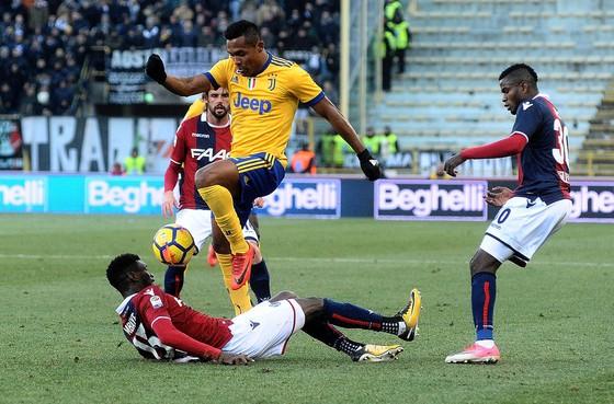 Hậu vệ Alex Sandro (Juventus) tránh cú tắc bóng gai góc của các hậu vệ Bologna. Ảnh: Getty Images.