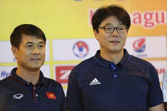 HLV Hữu Thắng (trái) và đồng nghiệp Hwang sun-Hong (Hàn Quốc) trao đổi về trận đấu
