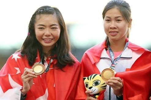 Việt Anh (phải) và VĐV của Singapore phải chia chung HCV nhảy cao nữ. tác giả: ĐÔNG HUYỀN