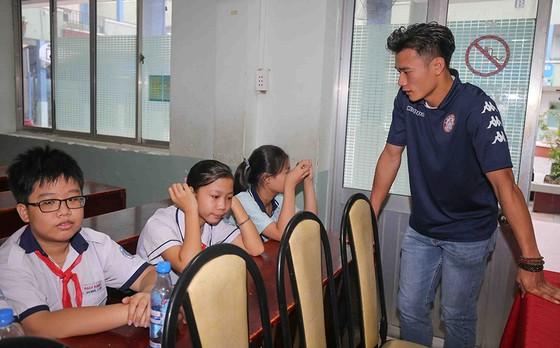 Thủ môn Bùi Tiến Dũng và đội trưởng Văn Thuận sẻ chia  với học sinh gặp tai nạn trường THCS Bạch Đằng  ảnh 3