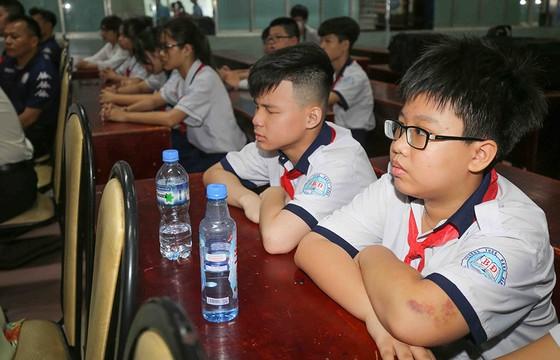 Thủ môn Bùi Tiến Dũng và đội trưởng Văn Thuận sẻ chia  với học sinh gặp tai nạn trường THCS Bạch Đằng  ảnh 2