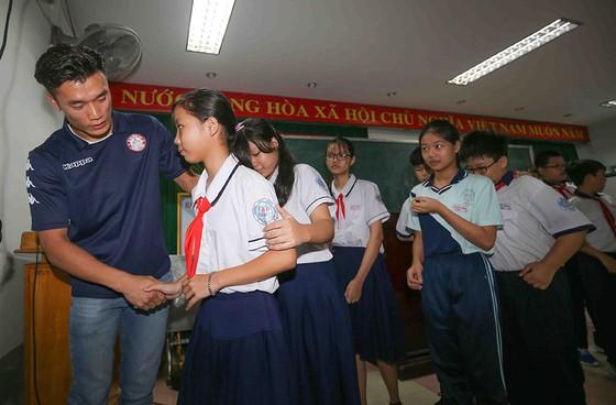 Thủ môn Bùi Tiến Dũng và đội trưởng Văn Thuận sẻ chia  với học sinh gặp tai nạn trường THCS Bạch Đằng  ảnh 4
