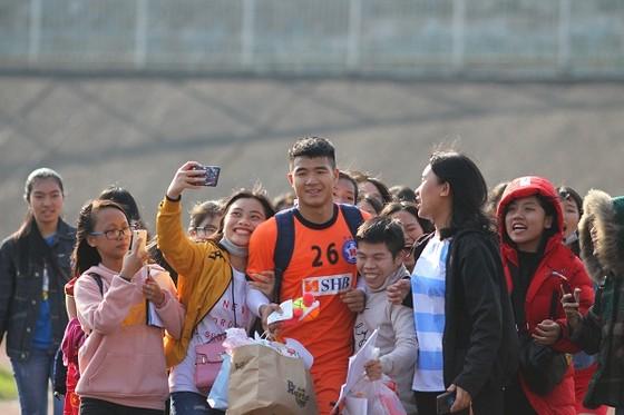 Đức Chinh trong vòng vây người hâm mộ bóng đá Huế. Ảnh: HỮU THÀNH