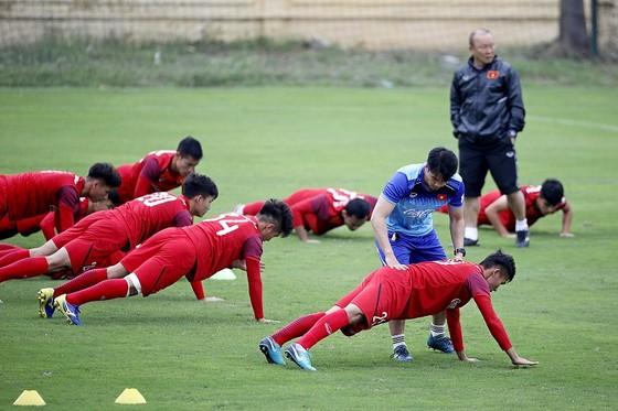 HLV thể lực hướng dẫn động tác căng cơ cho các cầu thủ. Ảnh: MINH HOÀNG