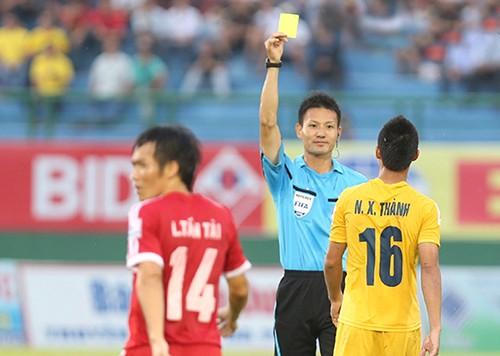 Trọng tài Sato Ryuji rút thẻ vàng với cầu thủ Thanh Hóa tại V-League 2014. Ảnh: QUANG LIÊM