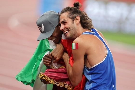 VĐV Tamberi đã ôm lấy đồng nghiệp Barshim để ăn mừng chiến thắng. Ảnh: REUTERS