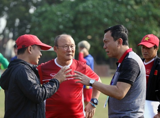 Phó chủ tịch VFF Trần Quốc Tuấn trao đổi cùng Ban huấn luyện trên sân tập. Ảnh: Đoàn Nhật