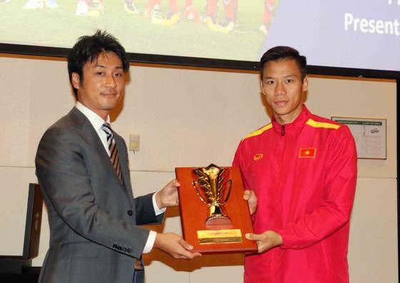 Thủ quân Quế Ngọc Hải đại diện toàn đội nhận kỷ niệm chương từ AFC. Ảnh: A.K