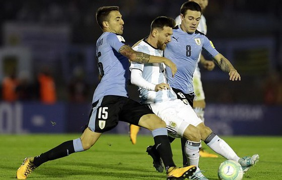 Messi trong vòng vây của hậu vệ Uruguay. Ảnh: AP