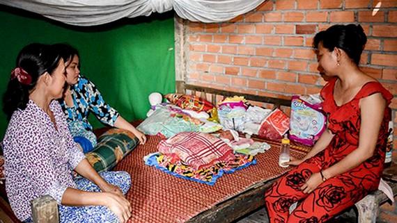 Người thân ông Trần Văn Bảnh chăm sóc bé sơ sinh bị bỏ rơi. Ảnh: NHẬT MINH