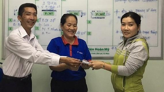 Bà Đoan (giữa) trao trả lại tiền cho chị Nguyễn Thị Thùy Dương