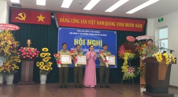 Đại diện tập thể Đội QLTT số 1,2,3 nhận bằng khen của UBND TPHCM