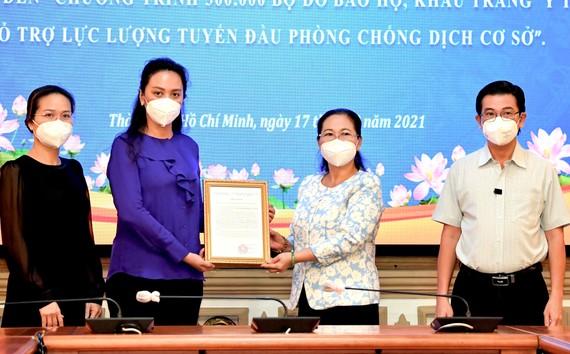 Chủ tịch HĐND TPHCM Nguyễn Thị Lệ tiếp nhận và trao thư cám ơn Công ty Bảo trợ Tập đoàn Vạn Thịnh Phát. Ảnh: VIỆT DŨNG