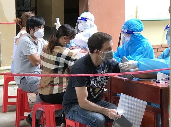 Ông Wesly (người Canada, áo đen) đang được kiểm tra lại sau khi tiêm ngừa vaccine. Ảnh: KP