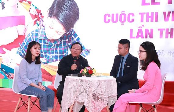 Nhà thơ Trần Đăng Khoa giao lưu với các em học sinh tại buổi lễ phát động. Ảnh VNP