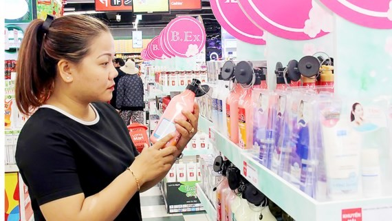 A customer is choosing cosmetics at a supermarket. (Photo: SGGP)