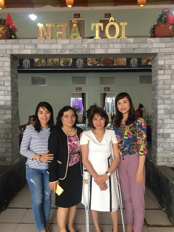 My Home: Trang stands with customers outside her restaurant.— Photo courtesy of Nguyen Thi Dai Trang