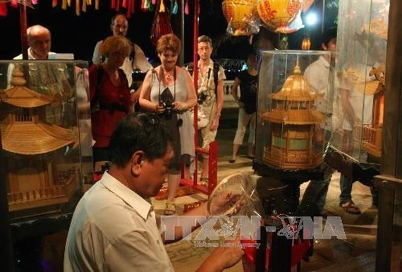 Foreign tourists visit a booth at the previous edition of the craft festival (Photo: VNA)