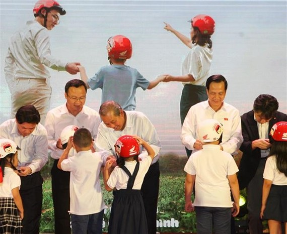 Deputy Prime Minister Truong Hoa Binh (third from left) presents a helmet to a first grader on June 12 (Photo: VNA)