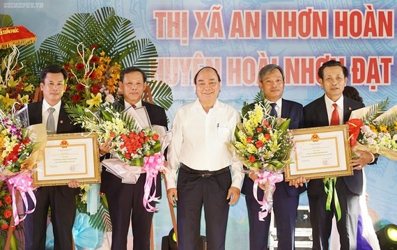 PM Phuc ( white) gives certificates to recognize the two communes to achieve the government's new rural plan (Photo: SGGP)