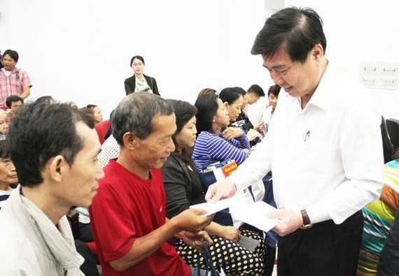 Chairman of Ho Chi Minh City People's Committtee Nguyen Thanh Phong gives presents to poor dwellers on occasion of Tet holiday 2019  (Photo: SGGP)