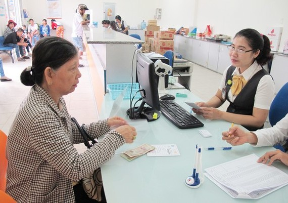 An elderly woman receives retirement salary and insurance in a post office in Binh Chanh Dsitrict (Photo: SGGP)