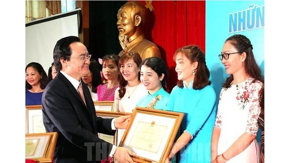 Minister Nha gives certificates of merit to outstanding teachers at the ceremony (Photo: SGGP)