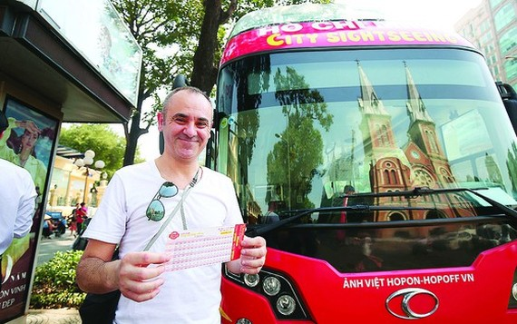 A foreign tourist buys a fare for hop-on hop-off tour in HCMC (Photo: SGGP)